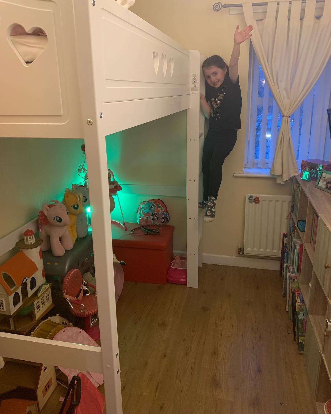 boxroom space saving ideas - 6 year old Sydney stood on the ladder of her new cabin bed, looking very excited.