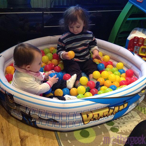 baby girl and toddler boy sat in batman paddling pool, filled with balls in their playroom.