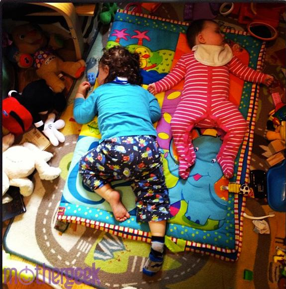 toddler boy and baby girl napping beside each other on playroom floor, surrounded by toys