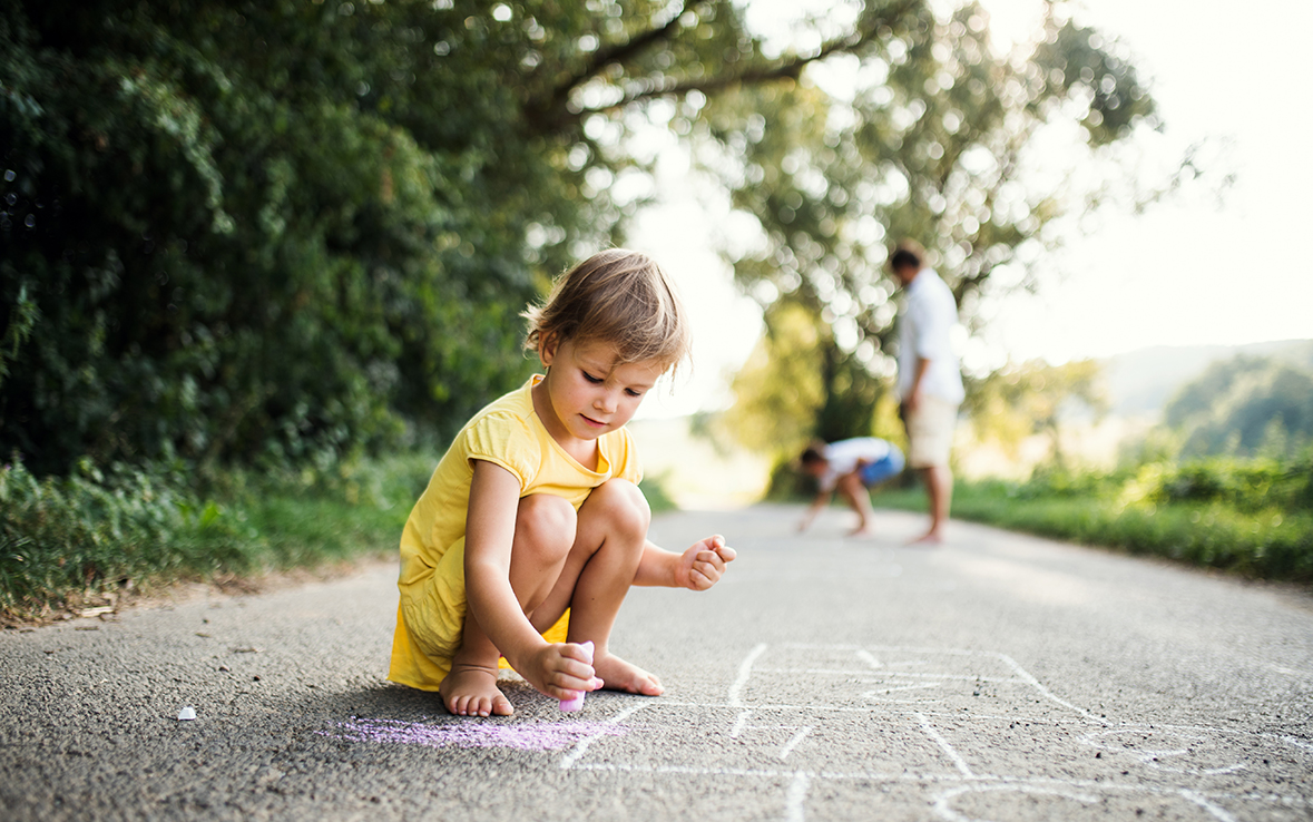 A small cute girl on a road in countryside in sunny summer nature, drawing with chalk.