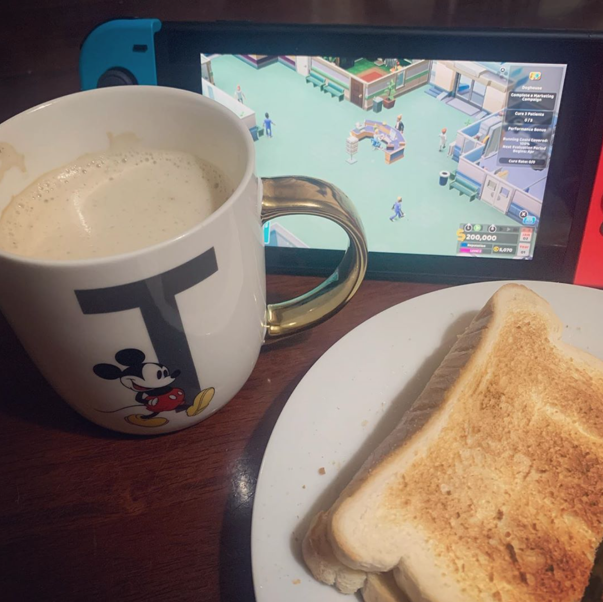 Nintendo Switch with two point hospital on the screen, a cup of coffee at the side and a slice of toast nearby. Is the Nintendo Switch educational?