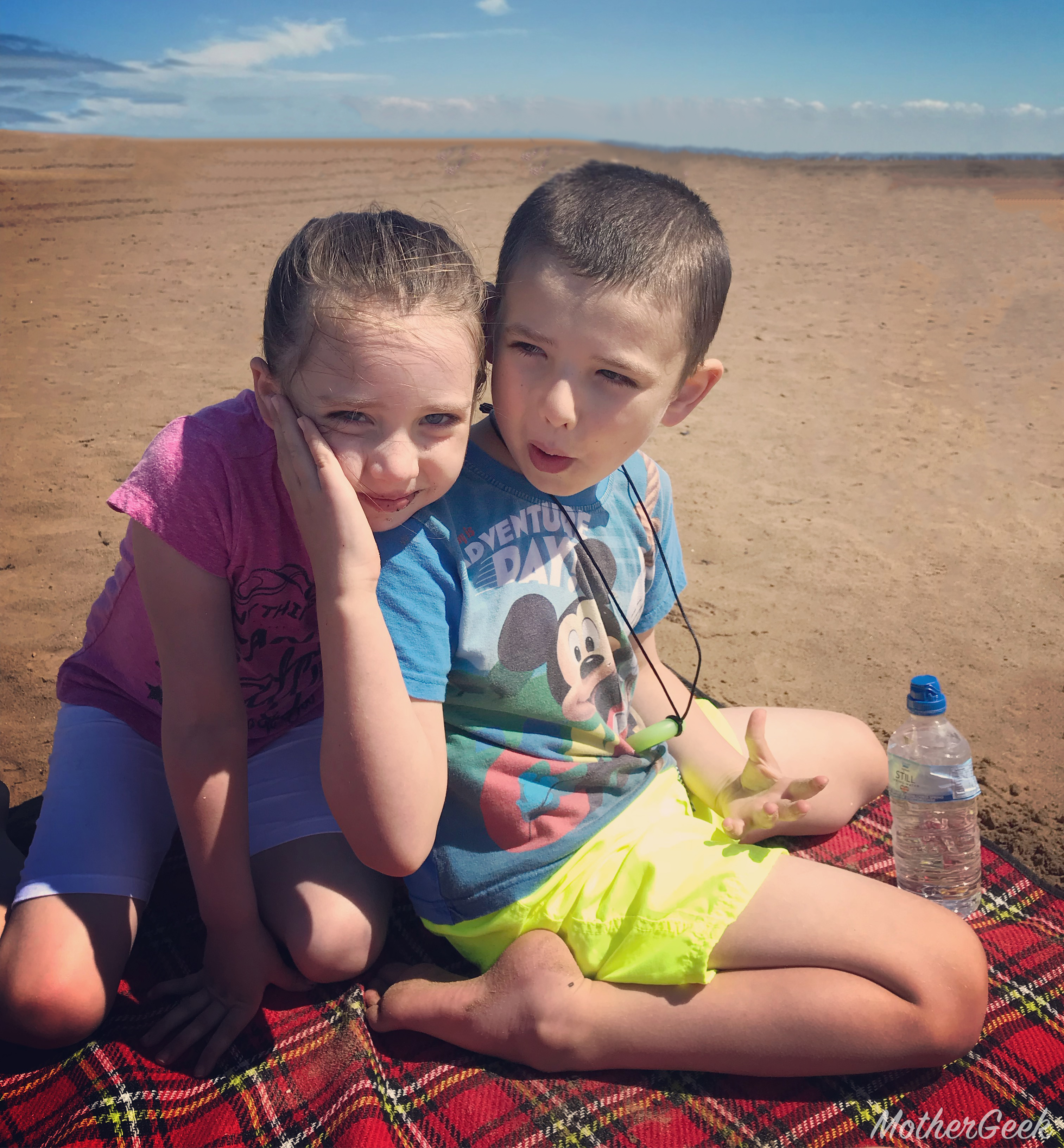 goals for 2019 - 2 kids sat on picnic blanket on the beach.