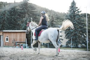 adult on a horse in helmet and boots