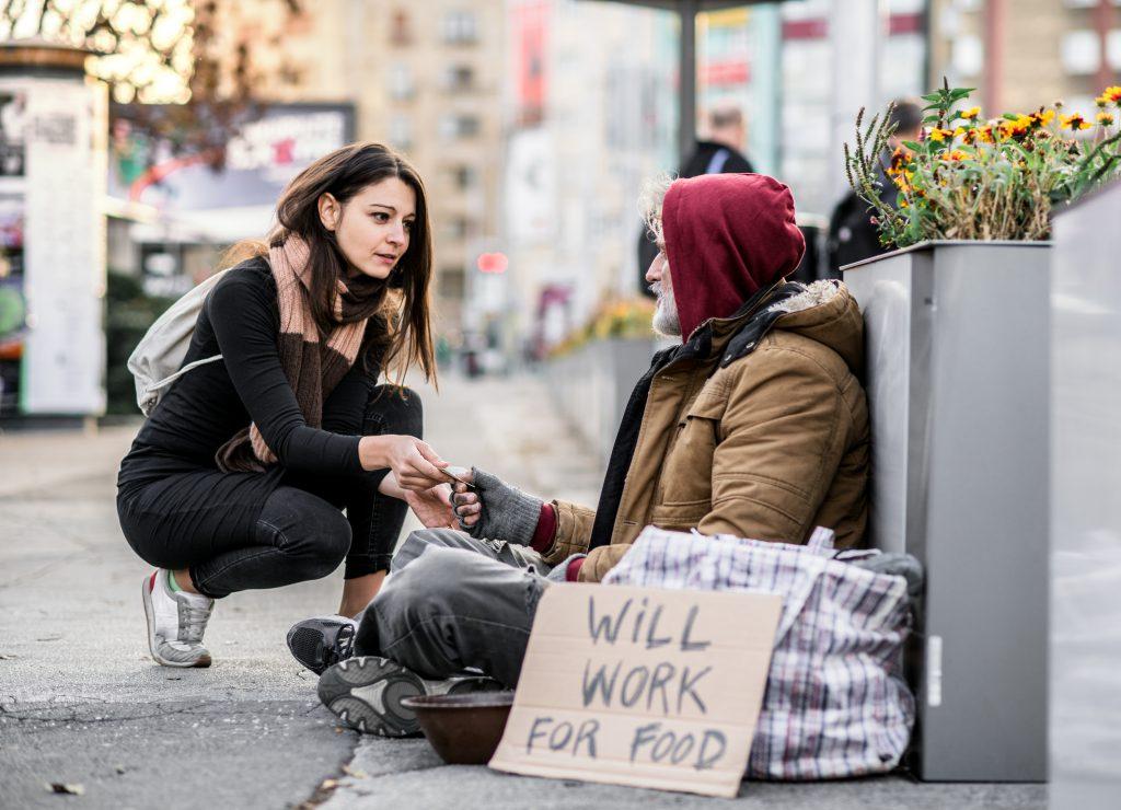 teach kids the value of money - girl giving homeless man some money