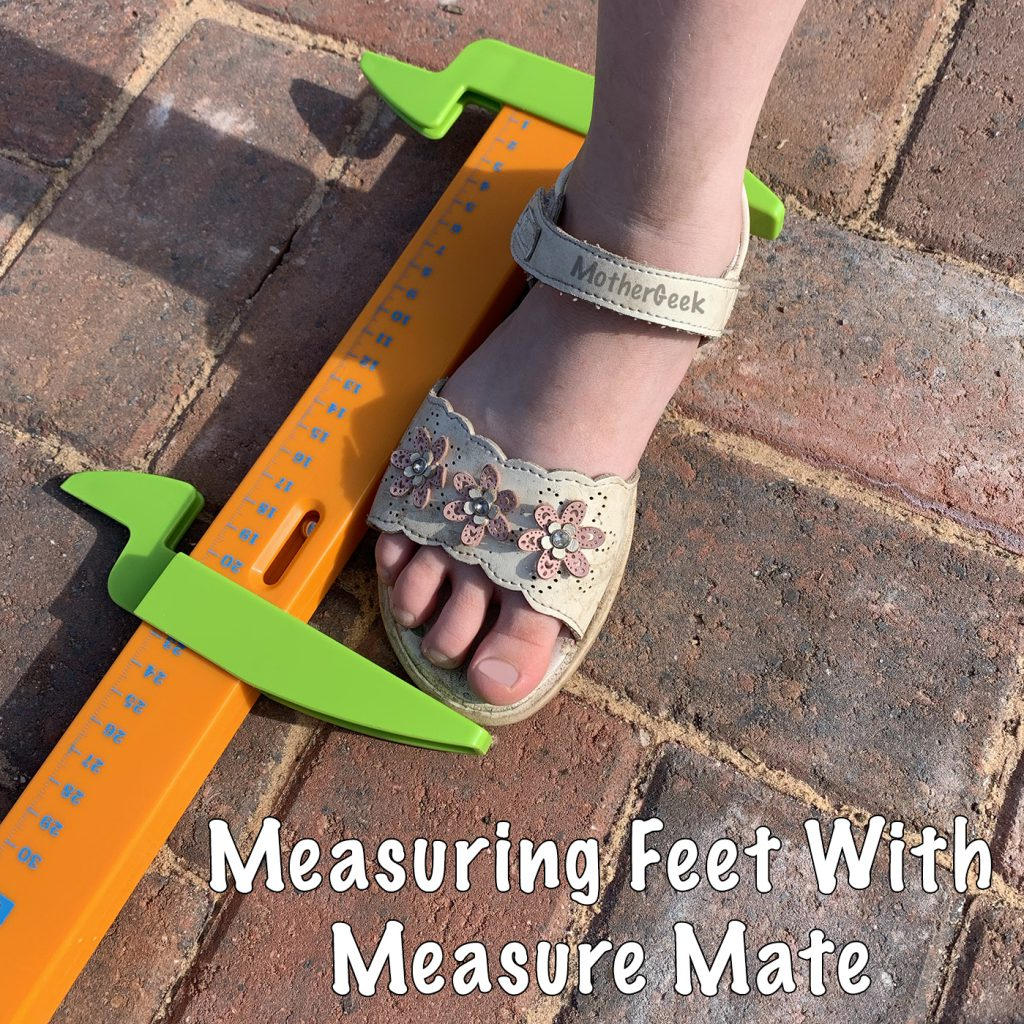 measure mate lay on a brick patio, measuring a kid's foot in a white sandal.