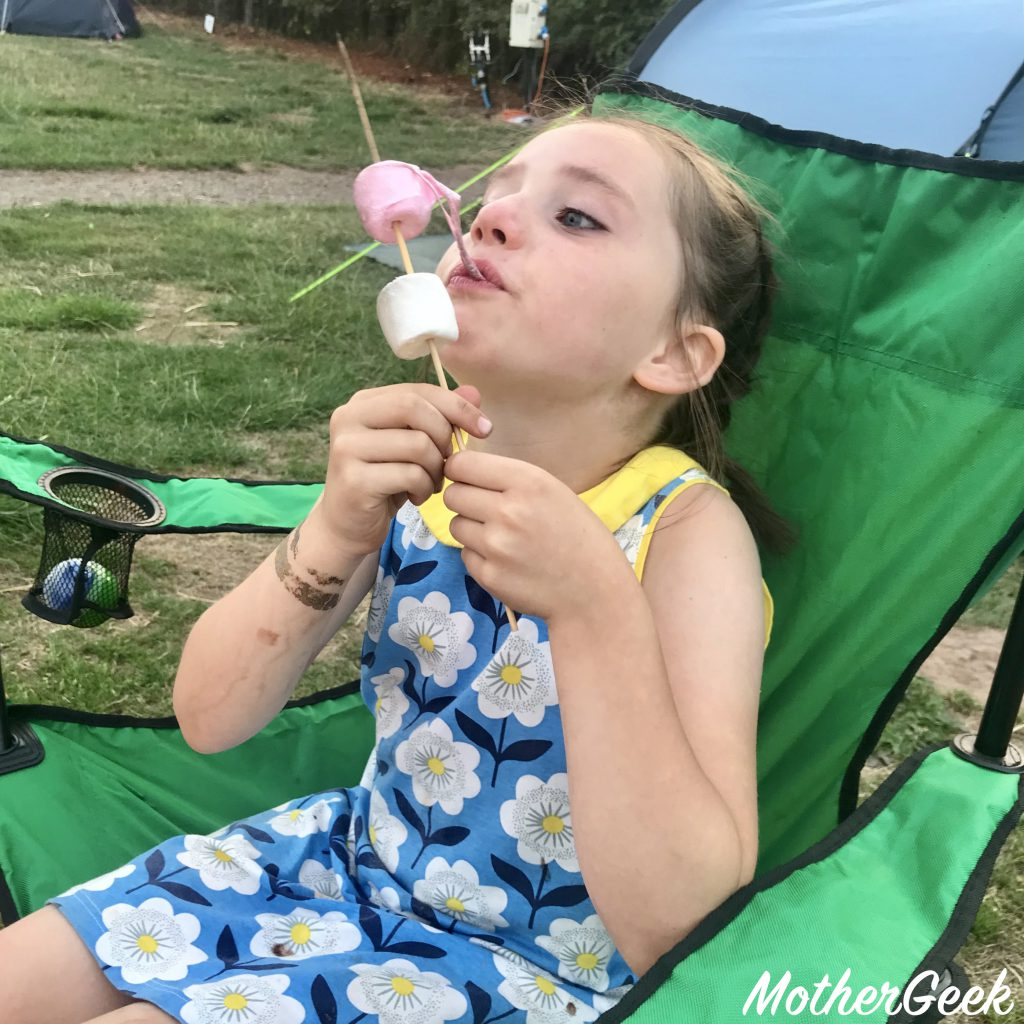 girl eating toasted marshmallows while camping