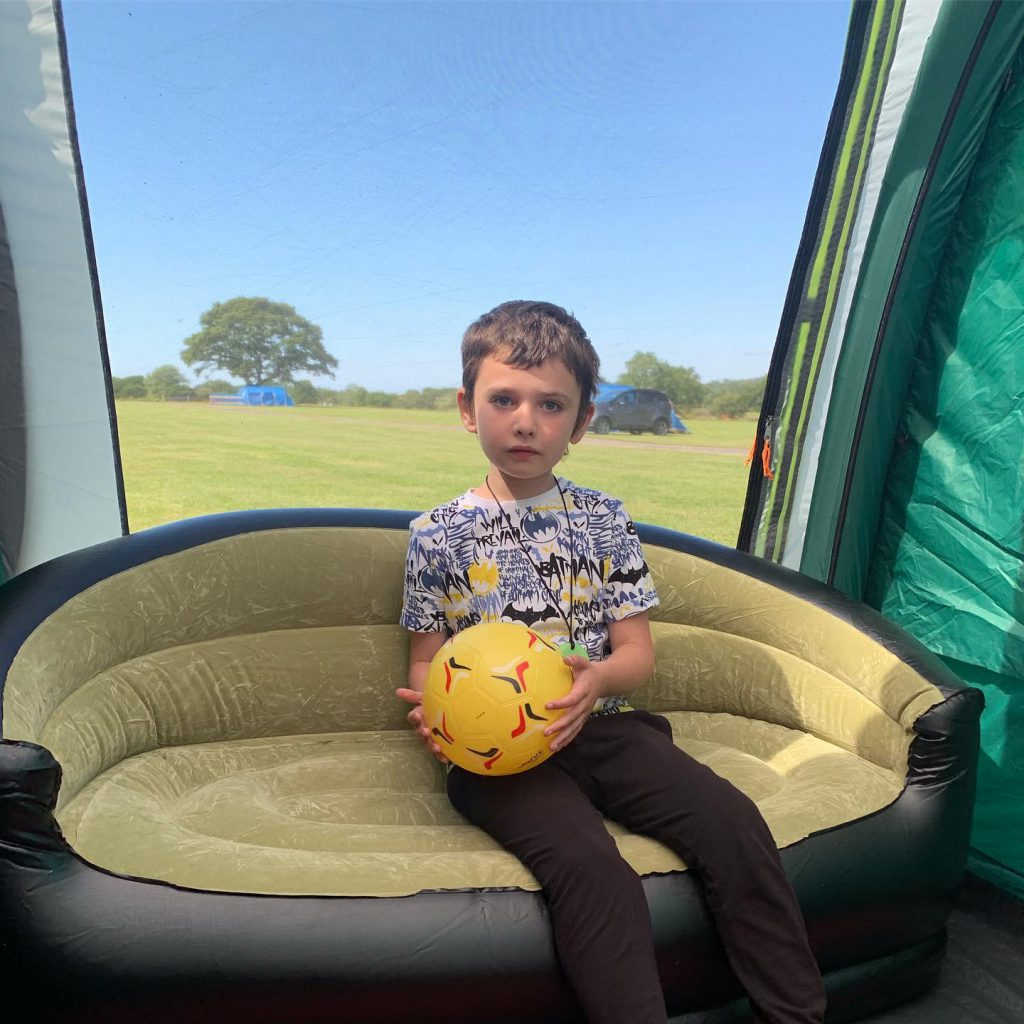 Sam sat on the inflatable sofa inside the tent