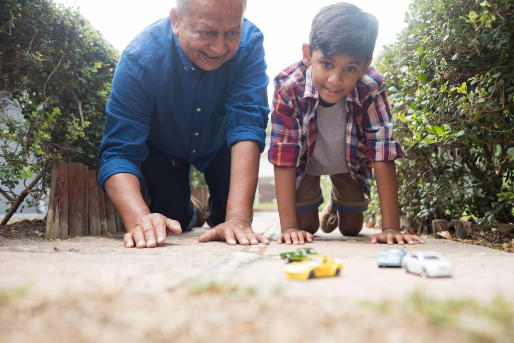 do dads ever grow up? Grandad playing toy cars with grandson