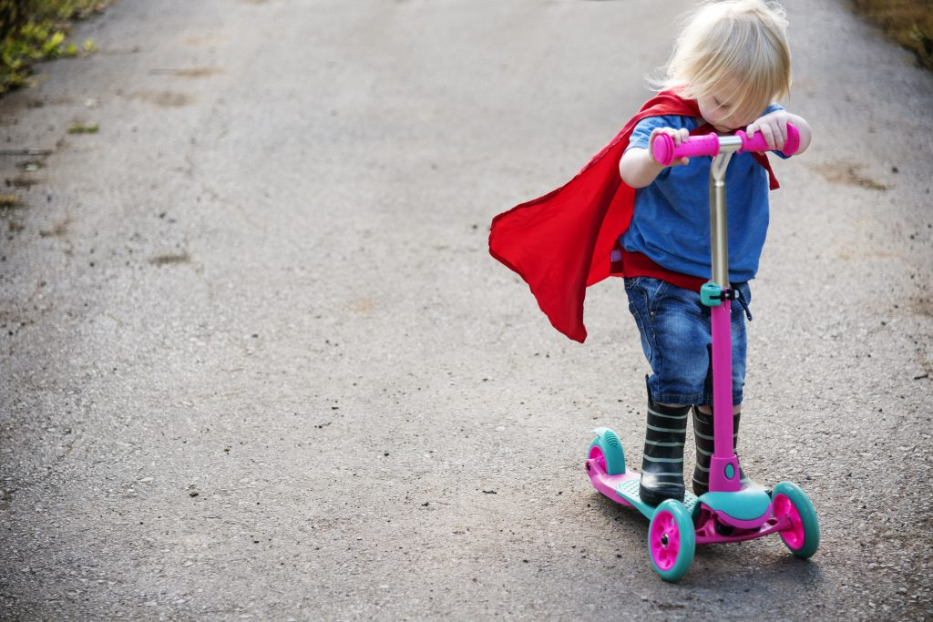 toys that get kids outdoors - young kind wearing a cape, riding a scooter