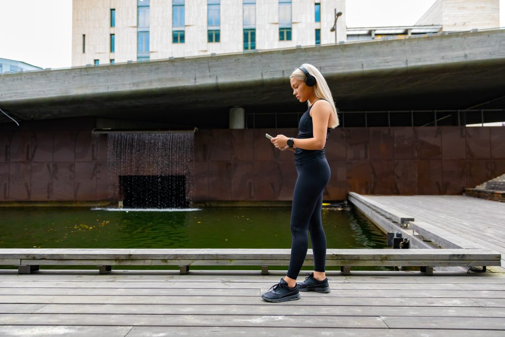 woman checking her Caloric Deficit and TDEE on phone before running