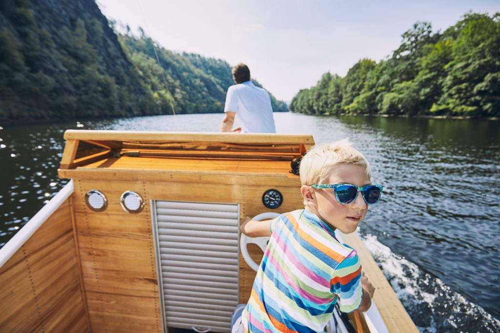 Boating Holidays with Children - young boy steering a motor boat