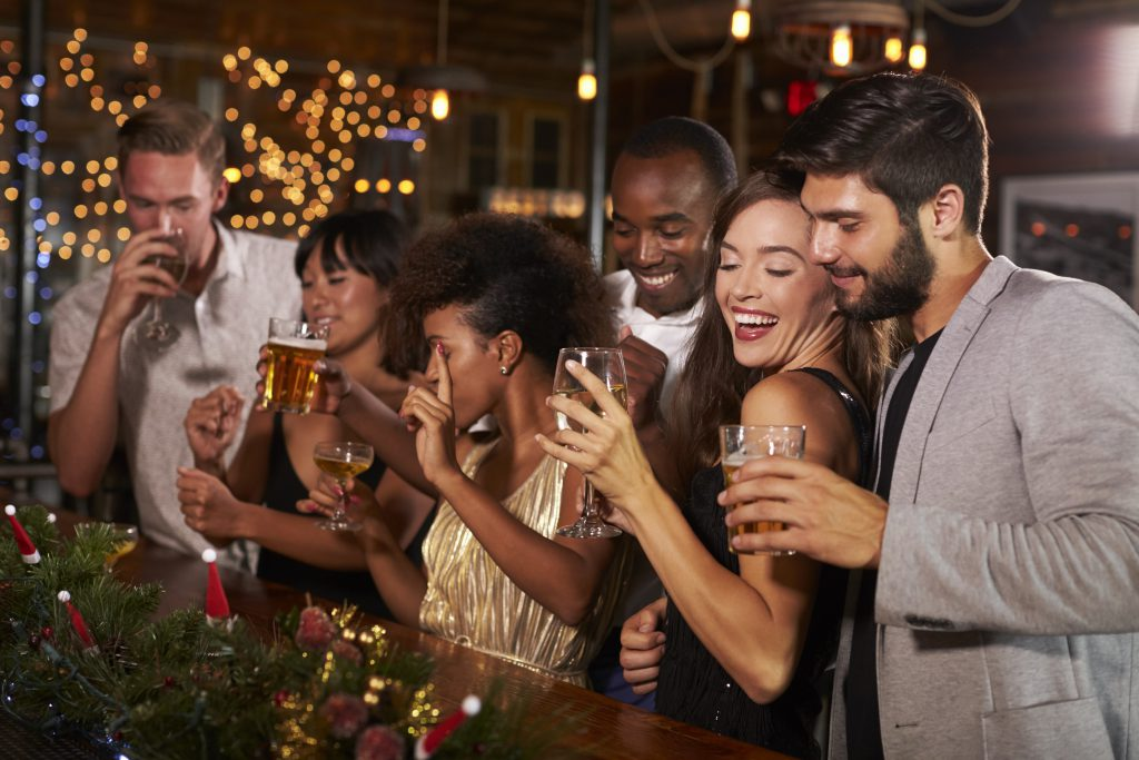 friends drinking in a bar at Christmas. Taken from blog post titled Planning A Christmas Night Out When You're Self Employed