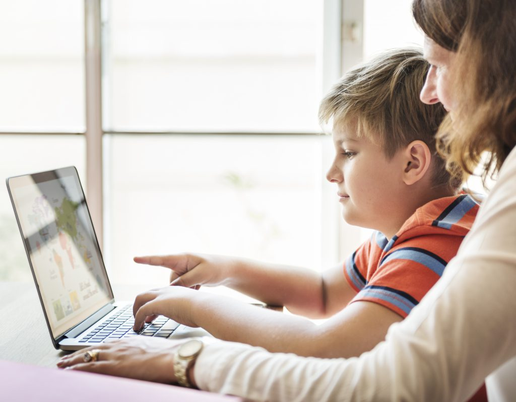 mum playing on a laptop with son to help him make it as a game designer