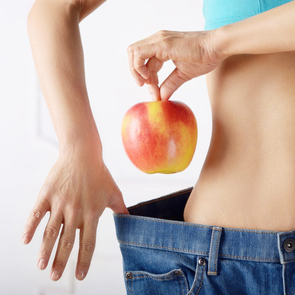 switching from veggie to vegan - woman with jeans too big on the waist, holding an apple near waist band