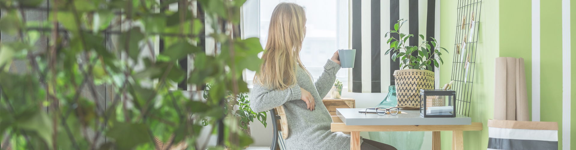 woman looking out of window while drinking coffee in home office... Ways to save money when working from home