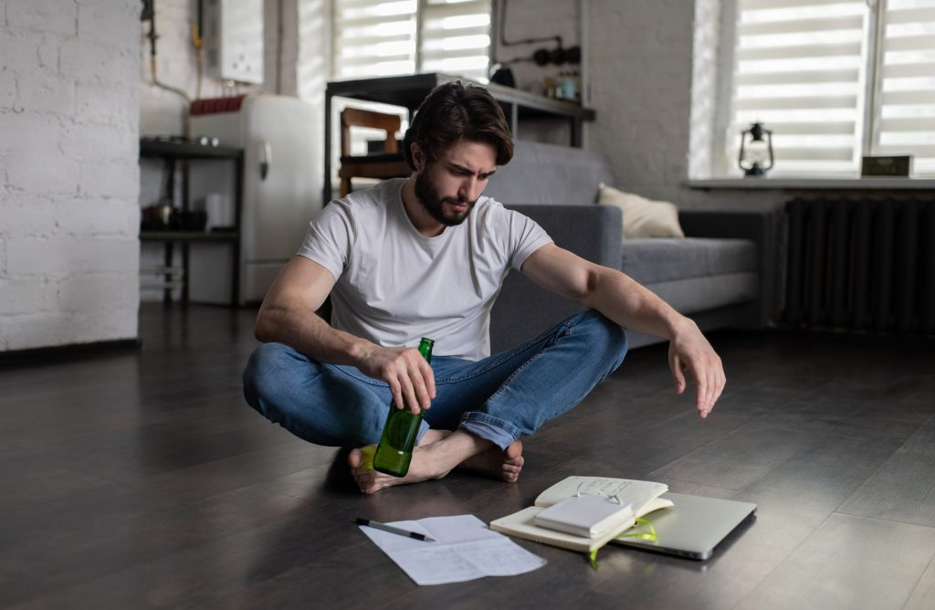 Stressed bearded man with bottle of beer sitting cross legged on floor near laptop and notebook and considering employment options while searching for job due to facing a professional disciplinary hearing for substance abuse