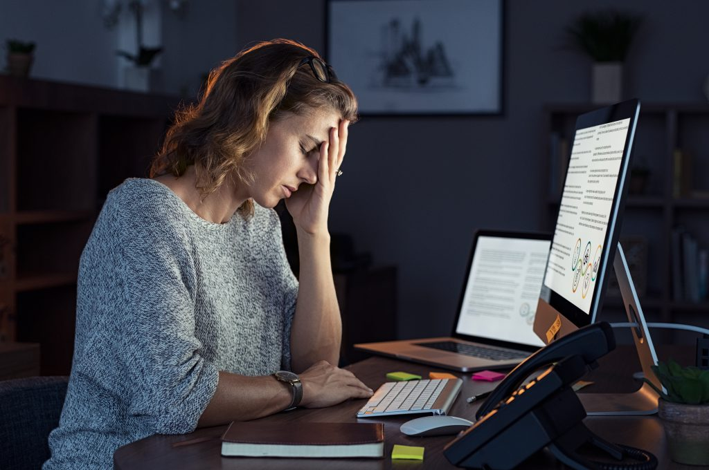 Stressed woman working over time as she's facing a professional discipline hearing for timekeeping
