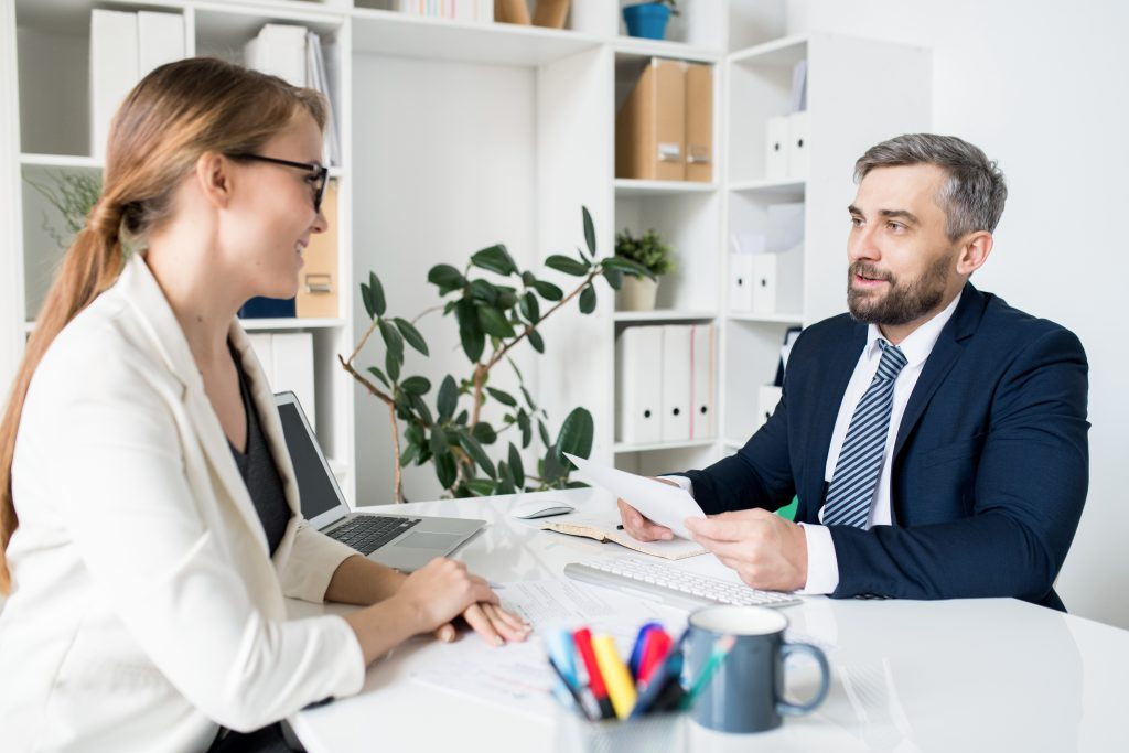Content handsome HR manager in formal jacket sitting at table with computer and reading resume of job candidate while interviewing her at meeting in office... Pros and Cons of Using Third-Party Providers