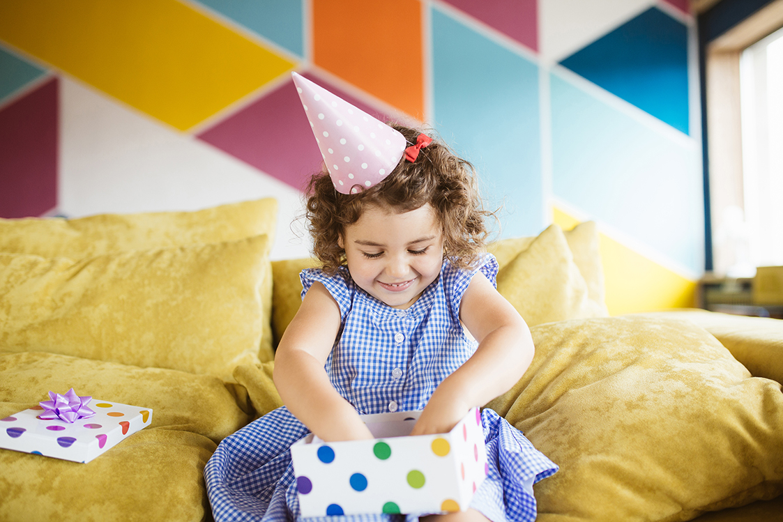 Cute smiling little girl with dark curly hair in birthday cap happily opening gift box on sofa at home, after parents tracking down the perfect toy