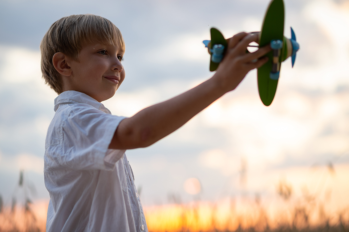 Boy in a white shirt with a plane in hands against sky. Kid holds a wooden airplane and dreams of being a pilot, on the nature. Happy child playing with a toy plane in nature during summer sunset.