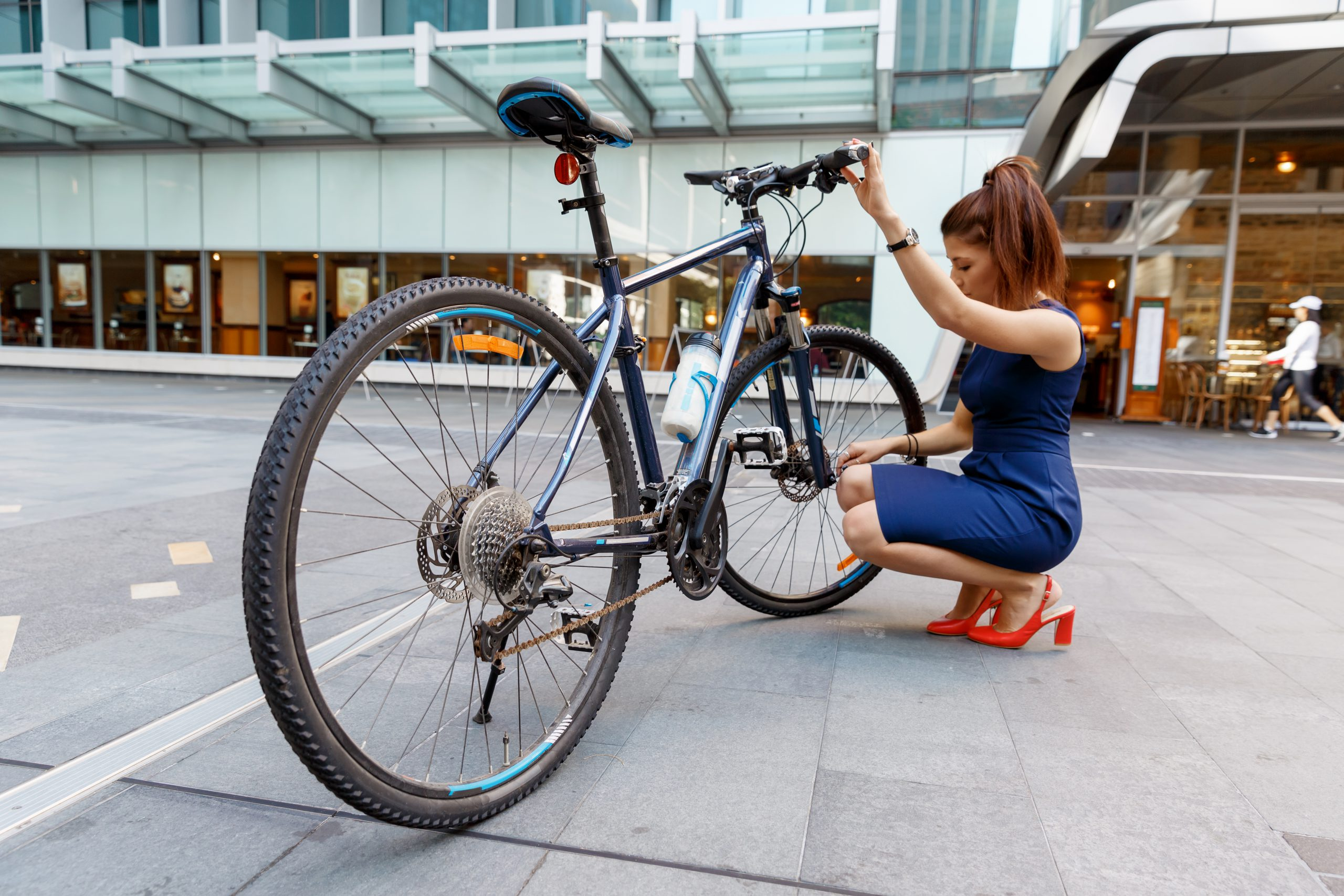 Young woman in business wear cycling to work in city