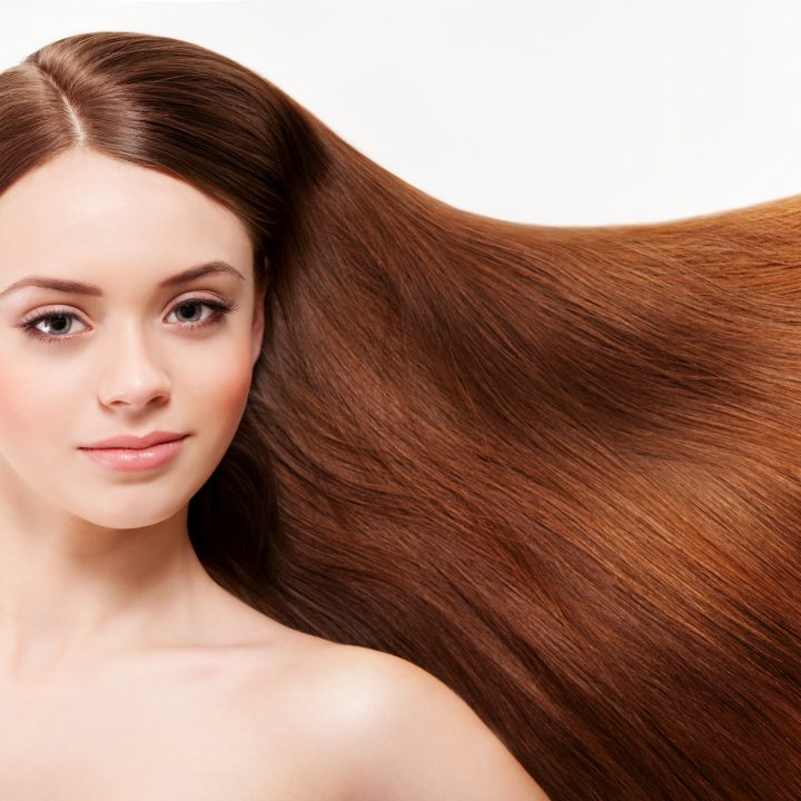 young woman with super shiny brown hair. She's used tips to keep your hair luscious during Winter
