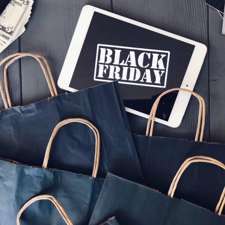 "flat lay of black paper shopping bags and an iPad saying ""Black Friday sale""."