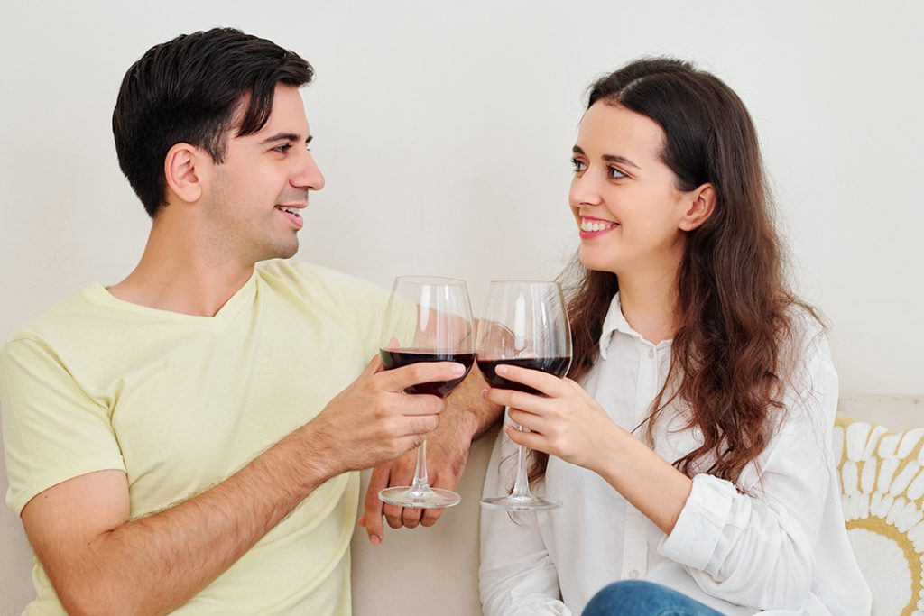Smiling boyfriend and girlfriend toasting with wine glasses and looking at each other when having date at home after reading Tips for a Romantic date night at home