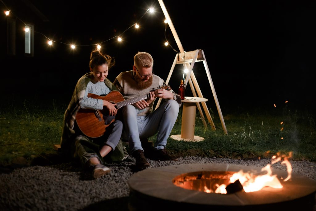 Man teaching girl play a guitar on autumn night picnic. Couple on date, after reading my Tips for a Romantic date night at home