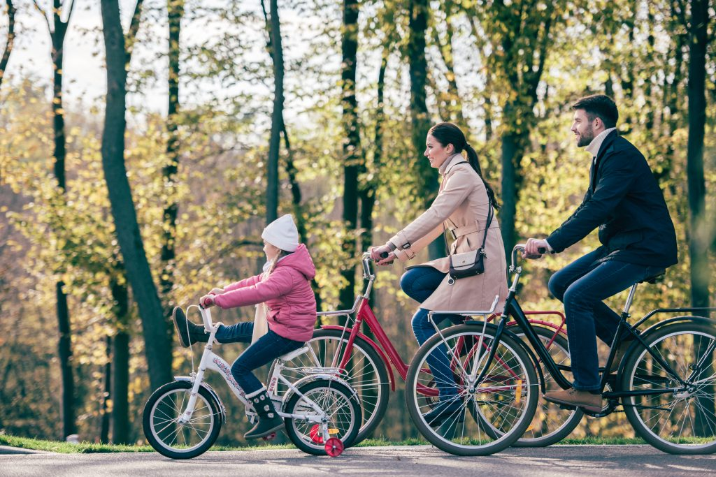 Side view of happy family riding bikes in park. They are out after reading about the benefits of outdoor play in Winter