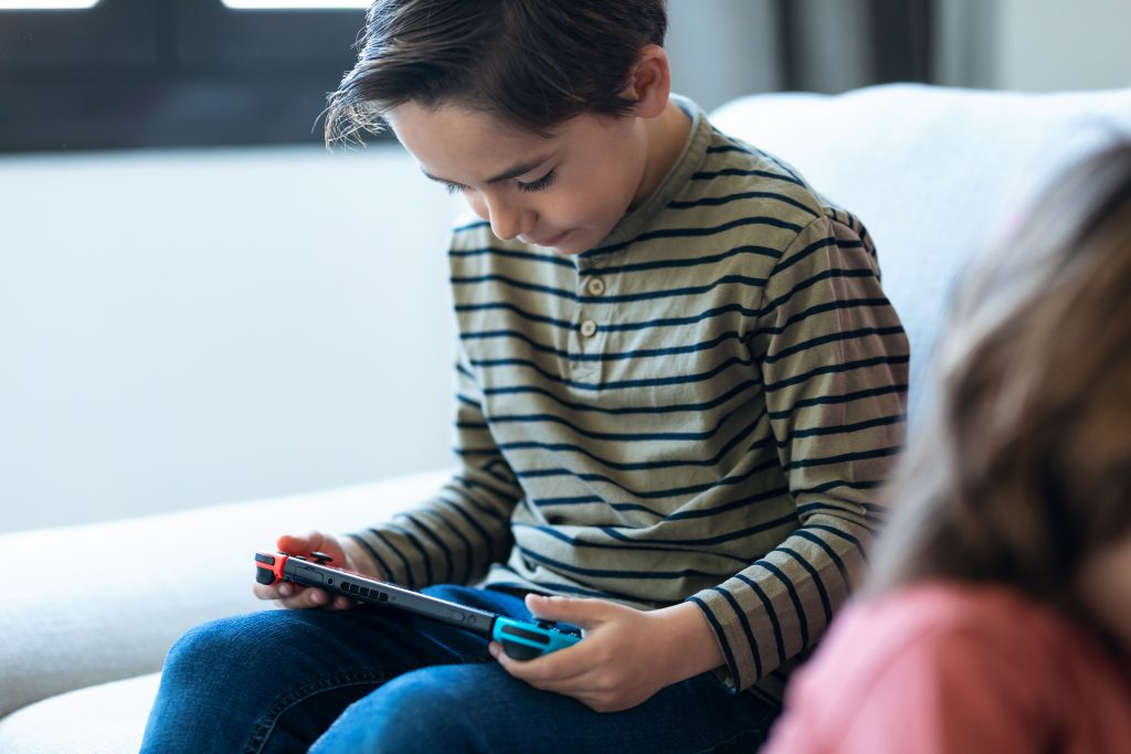 young boy playing Nintendo Switch at home. His parents answered Do You Really Need One of the New Consoles? and decided the switch was sufficient