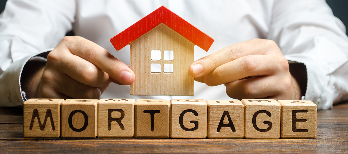 Wooden blocks with the word Mortgage and house in the hands of a businessman. The concept of buying a home on credit. Loan for apartments and housing. Interest rates. Creditor, debtor. Real estate