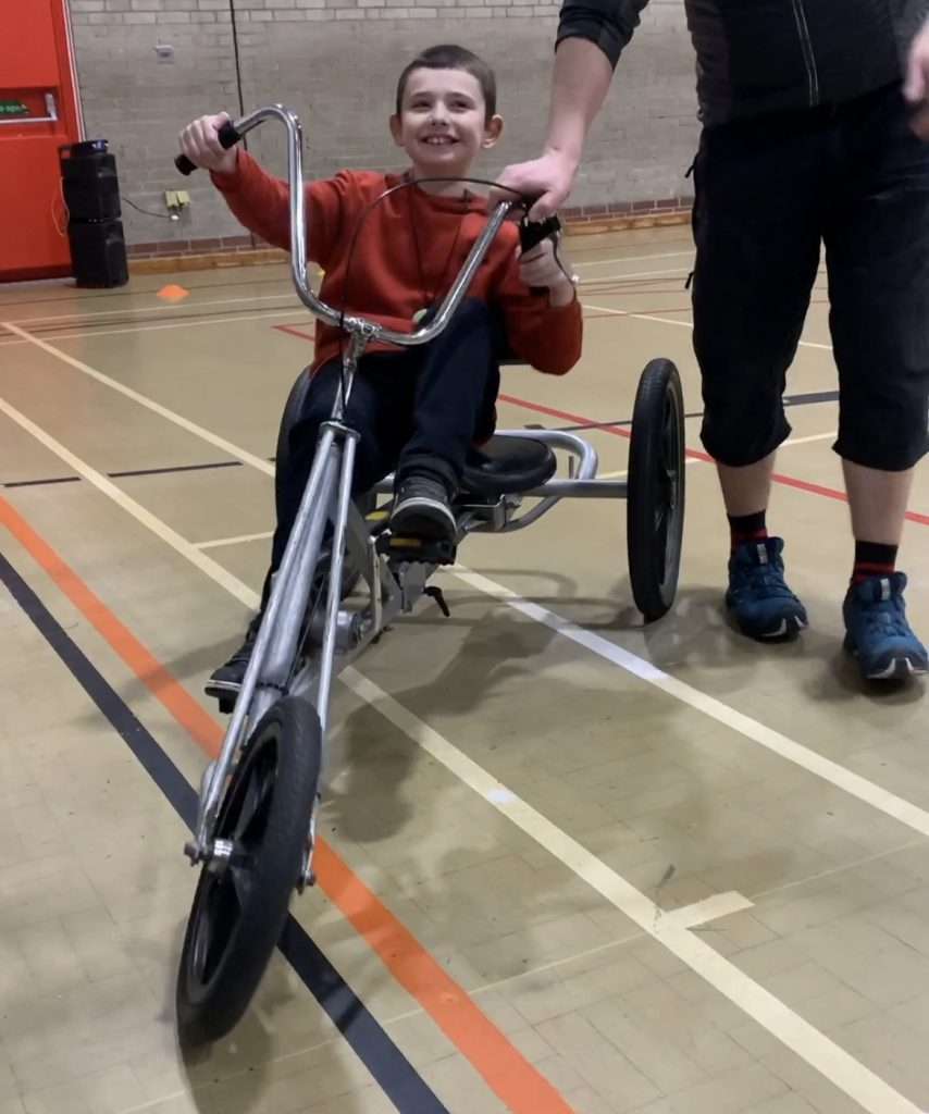 Autistic child on a trike, with a huge grin on his face. Proof of Why Trikes Are Great For Those With Disabilities