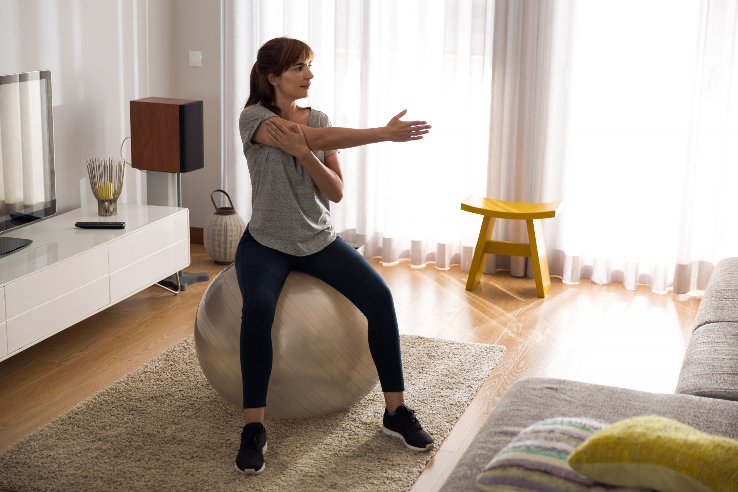 woman at home, exercising on a gym ball after reading tips on stick to your new fitness regime