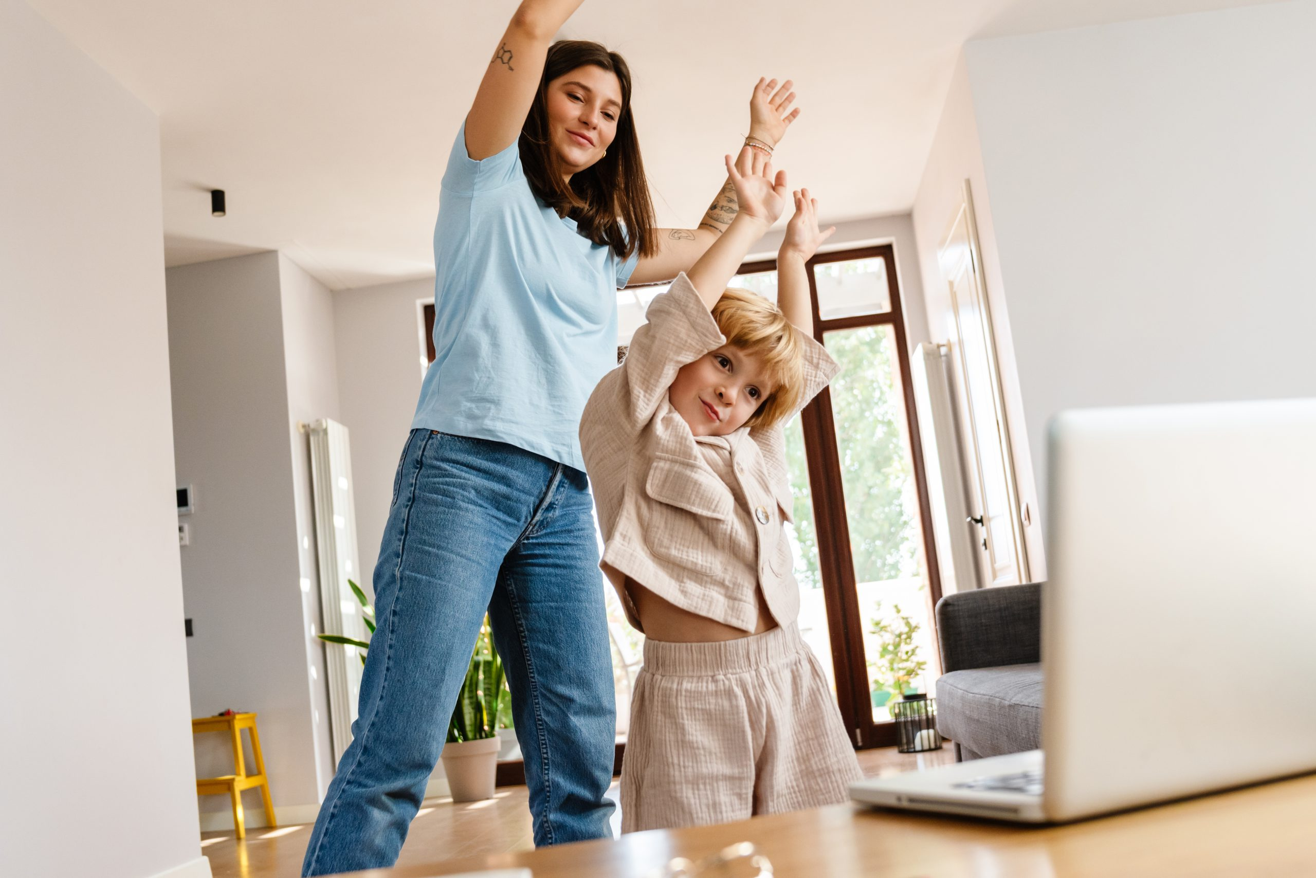 Photo of young positive beautiful woman at home with her son exercising while looking at laptop computer