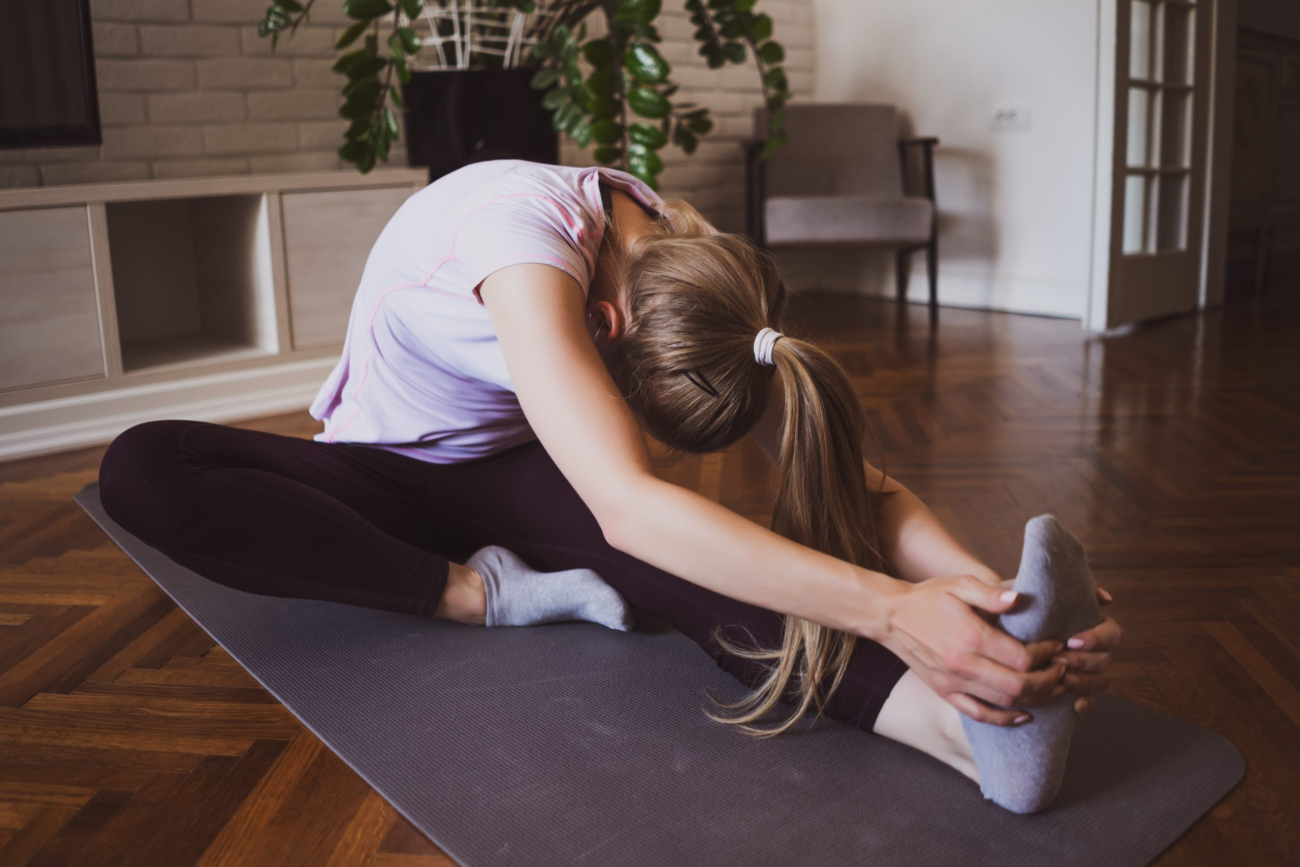 woman exercising at home on a yoga mat after reading tips to help you stick to your new fitness regime