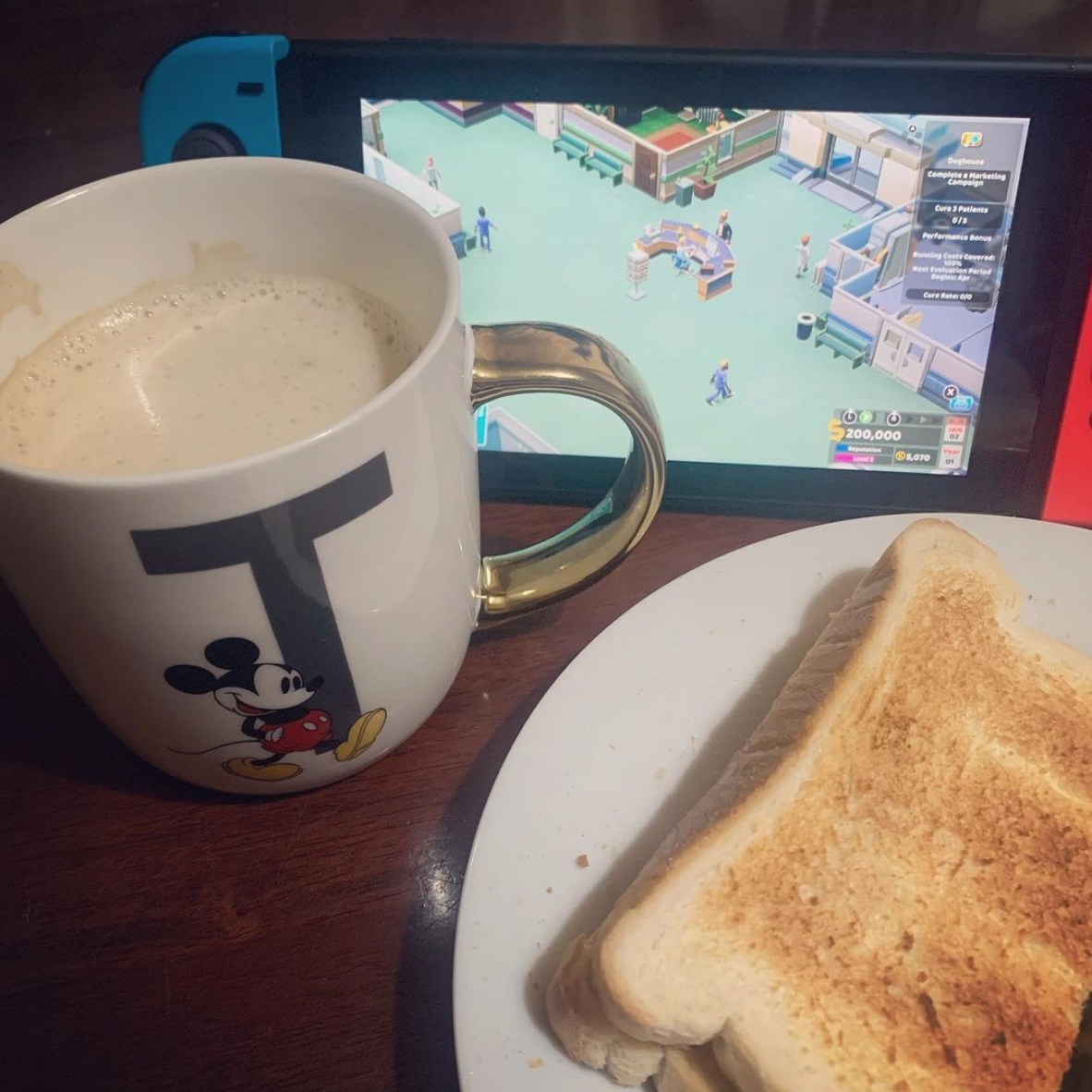 mug of coffee, plate with toast and a Nintendo Switch propped up, with Two Point Hospital on the screen... games that appeal to your geeky side