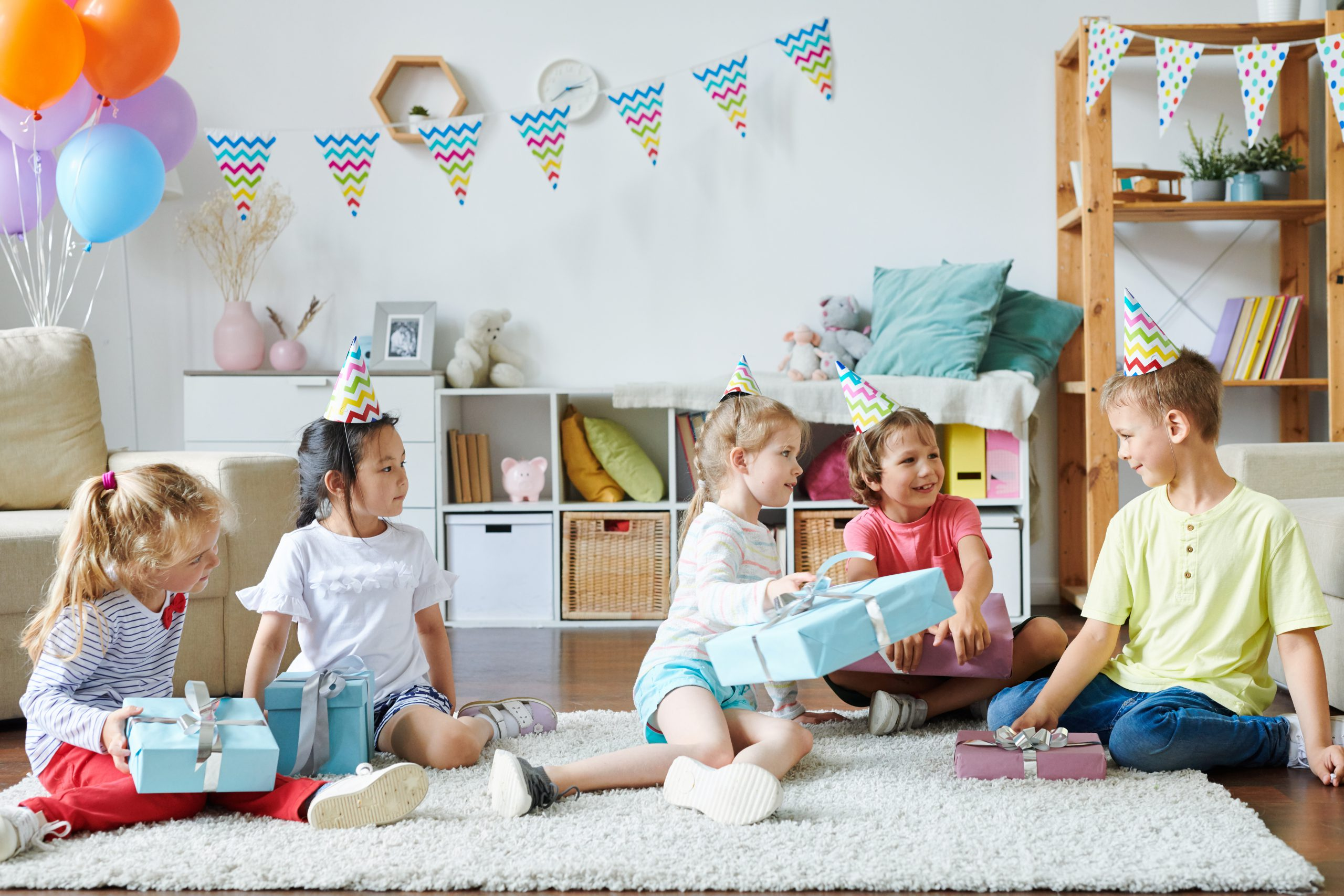 Group of happy adorable kids in birthday caps sitting on rug while going to unpack their gifts at home party