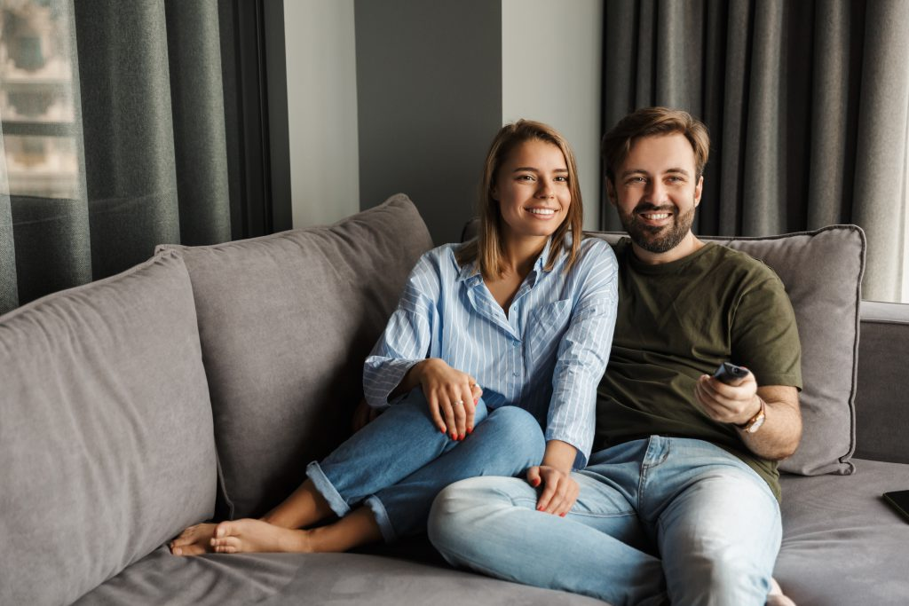Photo of joyful beautiful nice couple watching TV and using remote control while sitting on sofa at home