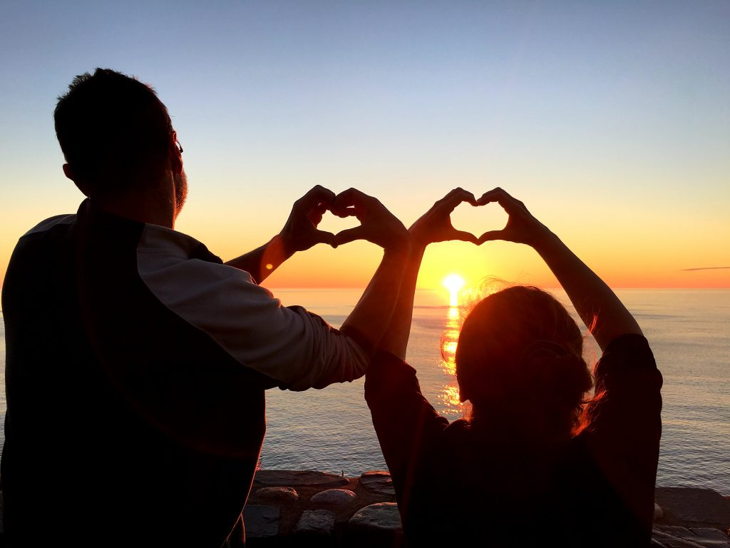 couple visiting the beach to make sunset love heart photos for the Perfect Anniversary Celebration