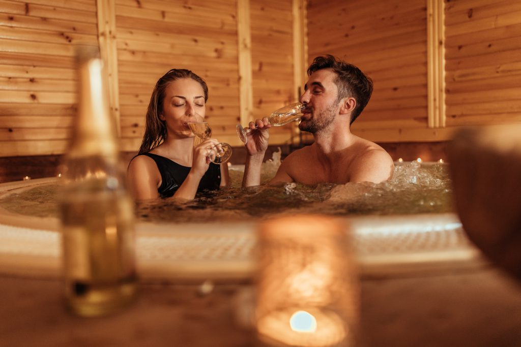 couple drinking champagne in a jacuzzi for their Perfect Anniversary Celebration