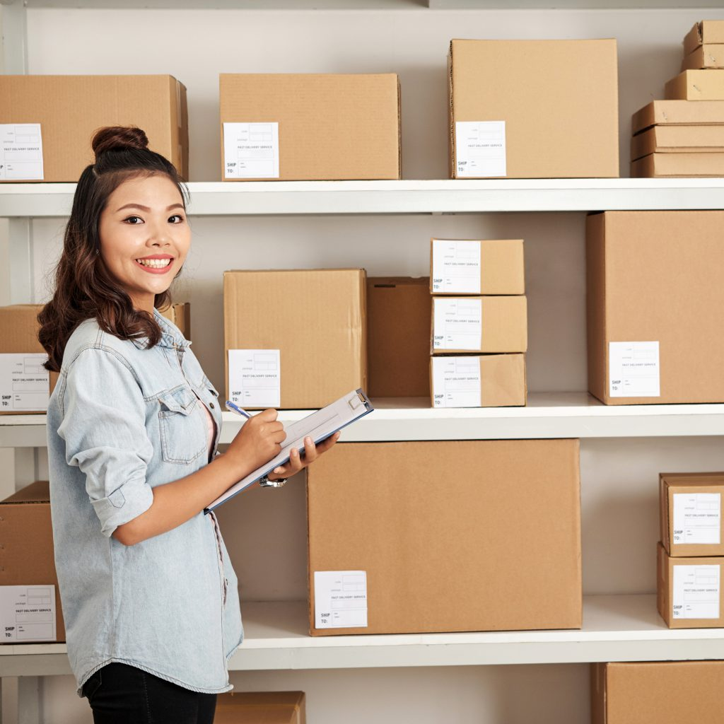 woman standing in former spare bedroom, now stockroom after learning how to scale up your home-based business