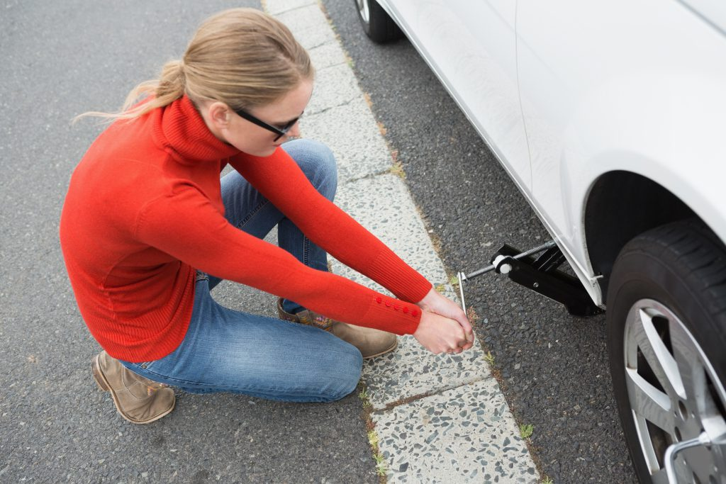 woman jacking up car, to change the tyre