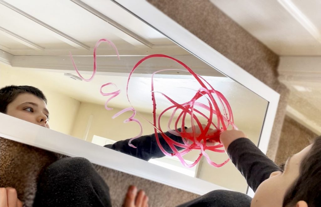 child drawing on a mirror with Little Brian Paint Sticks for a review