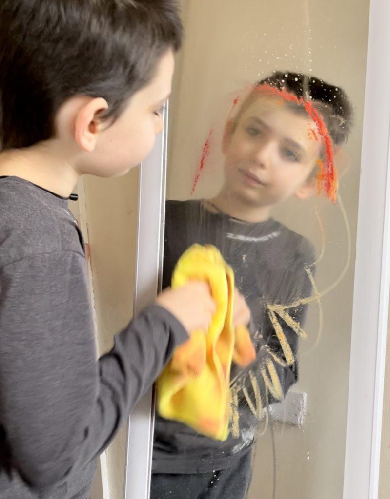 boy cleaning Little Brian Paint Sticks off a mirror