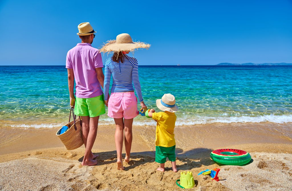Family on beach wearing straw sun hat. Young couple with three year old boy, inflatable ring, beach bag and toys. Clear sky. Summer family vacation. Sithonia, Greece.
