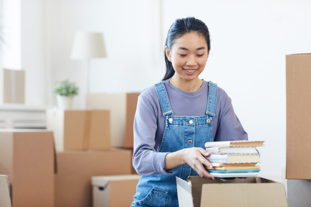 Portrait of young Asian woman packing books to cardboard boxes and smiling happily excited for moving to new house or dorm, copy space