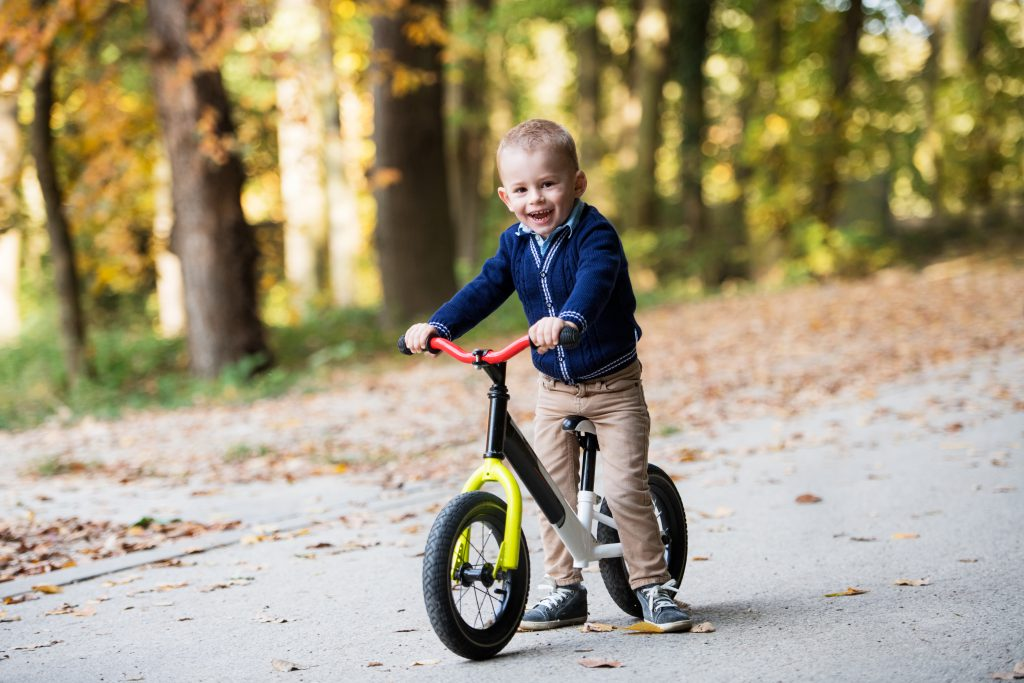young boy on balance bikes after their parents wondering how to teach a child to ride a bike