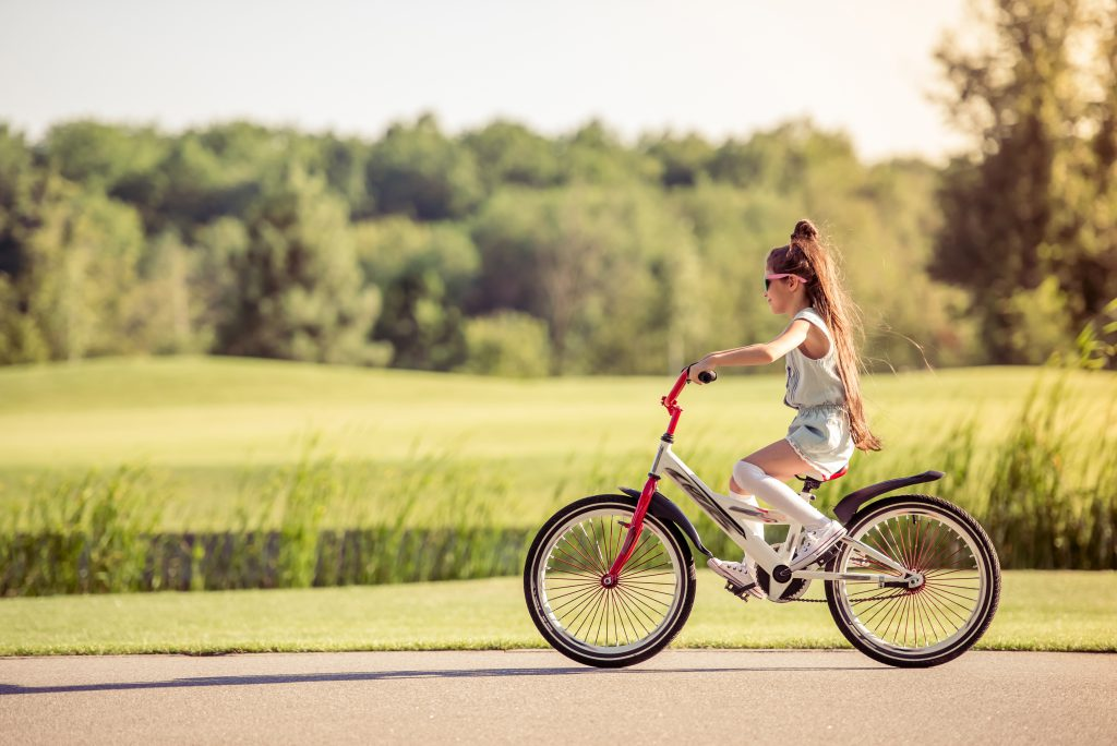 Side view of stylish little girl in sun glasses riding bike outdoors