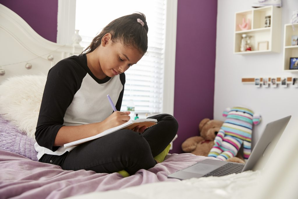 tween girl sitting on her bed writing in a notebook